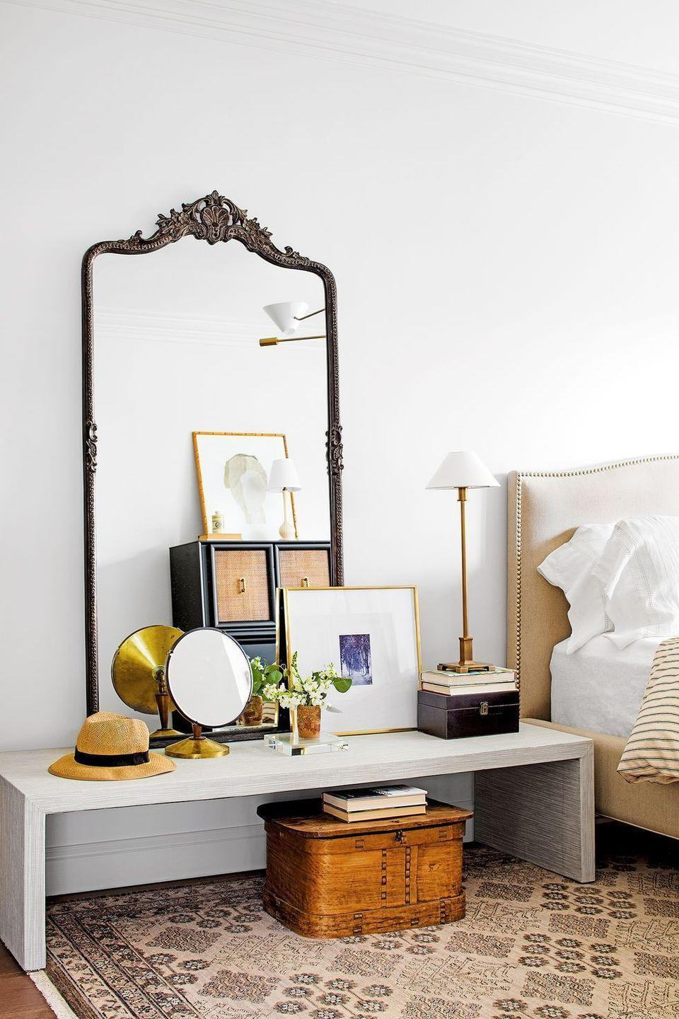 <p>Steal a trick from design pros and let a low-profile console table serve as a surface for propping oversized mirrors and framed art against your bedroom wall. Finish the look with a small floral arrangement and lamp.<br></p>