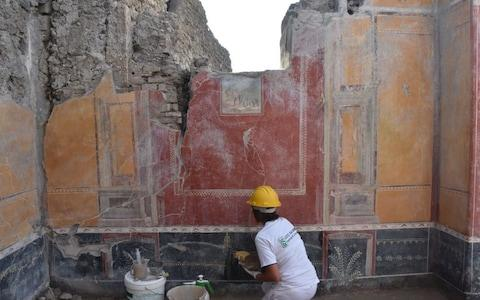 An archeologist works on restoring frescoes on a villa wall - Credit: Pompeii