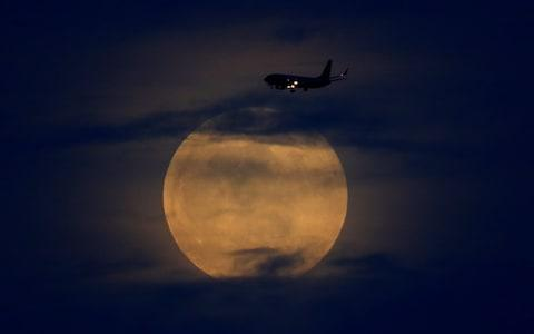 A plane passes as the moon rises through clouds before start of total lunar eclipse in California - Credit:  MIKE BLAKE/Reuters