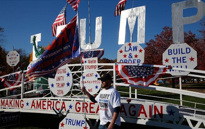 A man poses in front of a Trump sign as he waits to see US Republican Presidential nominee Donald Trump address supporters on November 6, 2016 in Sterling Heights, Michigan (AFP Photo/Jeff Kowlasky)