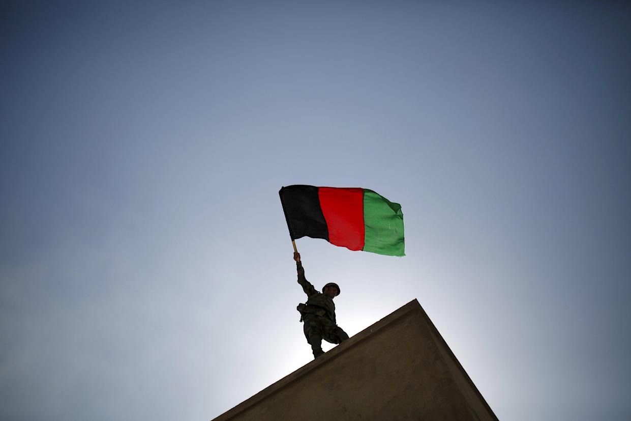 An Afghan National Army (ANA) officer holds an Afghanistan flag during a training exercise at the Kabul Military Training Centre in Afghanistan October 7, 2015. REUTERS/Ahmad Masood