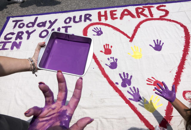 <p>People stamp their painted hands on a banner made by Chicago artist Greg Marchuk, in supporting of the victims of the shooting at the Pulse nightclub in Orlando, Fla., June 12, 2016. (EPA/Cristobal Herrera) </p>