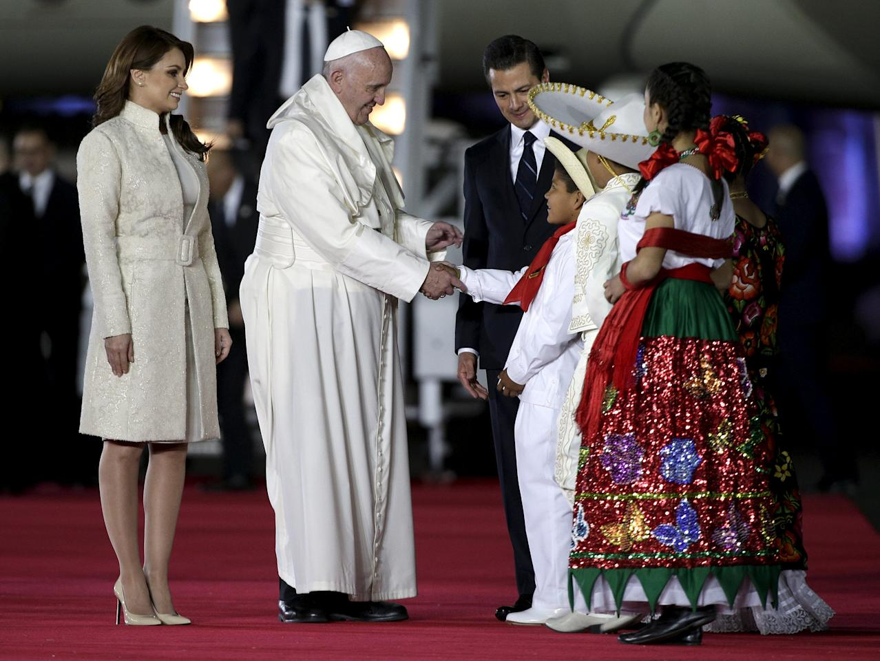Pope Francis greets children next to Mexico's President Enrique Pena Nieto and Mexico's first lady Angelica Rivera after his arrival in Mexico City