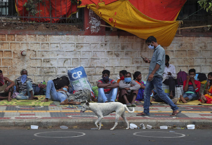 FILE - In this Tuesday, June 9, 2020, file photo, migrant workers from other states rest on a pavement as they wait for trains to their home states in Hyderabad, India. In just three weeks in June and July, India's confirmed cases shot up from the world's sixth to the third-worst hit country by the coronavirus pandemic, according to a tally by Johns Hopkins University. India's fragile health system was bolstered during stringent monthslong lockdown but could still be overwhelmed by an exponential rise in infections. (AP Photo/Mahesh Kumar A., File)