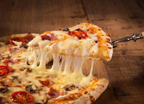 A spatula pulls up a slice of pizza with tomatoes and mushrooms.