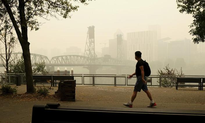 "<span class=""element-image__caption"">A pedestrian walks past the Willamette Bridge and downtown Portland, Oregon, on Wednesday.</span> <span class=""element-image__credit"">Photograph: Don Ryan/AP</span>"