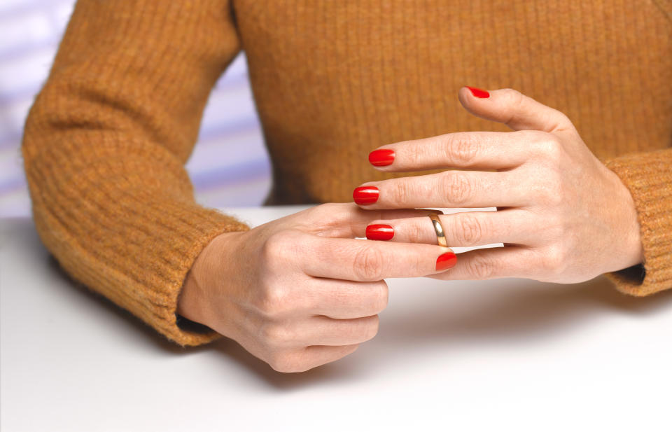 sad young lady removing her wedding ring after divorce decision