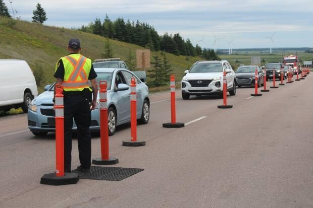 A peace officer directs traffic at the Aulac point of entry into New Brunswick from Nova Scotia in 2020. (Alexandre Silberman/CBC - image credit)