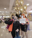 A passenger from New Zealand, second left, poses with drag queens as they welcome her at Sydney Airport in Sydney, Australia, Monday, April 19, 2021, as the much-anticipated travel bubble between Australia and New Zealand opens. (AP Photo/Rick Rycroft)