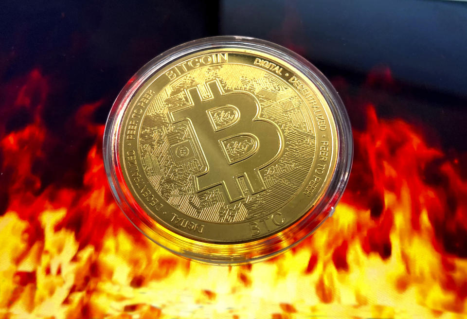A stylised image of a physical bitcoin floating above flames. Source: AP
