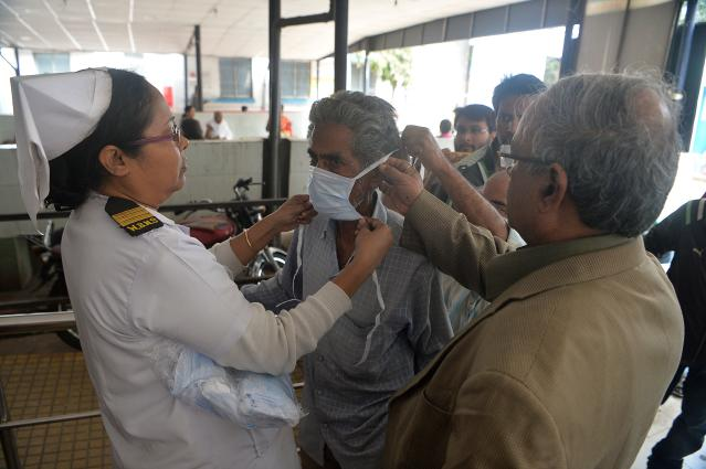 Doctors place a protective facemask on a patient coming with others to the outdoor patient department for an awareness event about the COVID-19 in Siliguri.