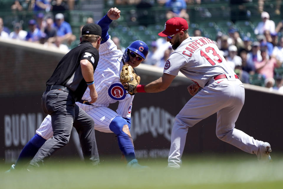 St. Louis Cardinals' Matt Carpenter (13) shows second base umpire Mike Muchlinski the ball after catching Chicago Cubs' Joc Pederson trying to steal second during the first inning of a baseball game Friday, June 11, 2021, in Chicago. (AP Photo/Charles Rex Arbogast)