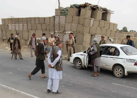 Afghan local police (ALP) keep watch at a checkpoint at Chardara district, in Kunduz province