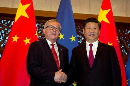 FILE PHOTO: European Commission President Juncker and Chinese President Xi shake hands in Beijing