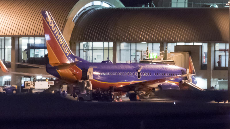 In this Monday, Feb. 12, 2018 photo, a Southwest Airlines plane sits it a gate after passengers had to evacuate before takeoff because of a fire at John Wayne Airport in Santa Ana, Calif. Federal Aviation Administration spokesman Allen Kenitzer says the blaze was in the airliner's auxiliary power unit and was extinguished with the plane's fire suppression system (Leonard Ortiz/The Orange County Register via AP)