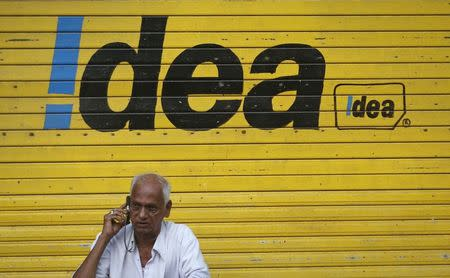 Man speaks on his mobile phone as he sits in front of a shop displaying the Idea Cellular Ltd's logo on its shutter in Mumbai
