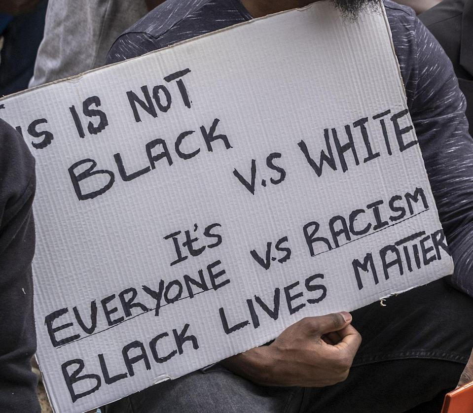 <p>A protester notes that this is not a sign of division between races, but a sign of unity against racial injustice. </p>