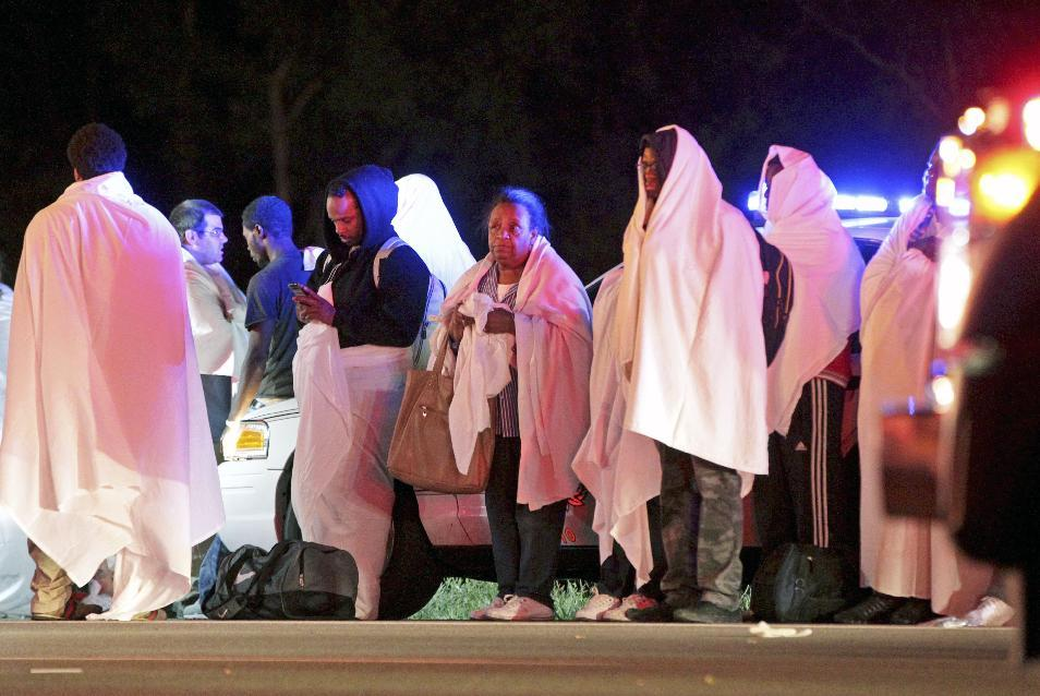 Passengers of an overturned Greyhound bus stand near the scene, Saturday, Sept. 14, 2013, on interstate I-75 in Liberty Township, Ohio. Authorities say that at least 34 people have been hurt, with injuries ranging from minor to severe. (AP Photo/Dayton Daily News, Nick Daggy)