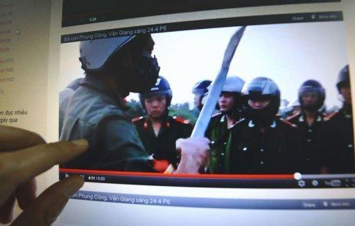 A man watches a video posted on the blog of Dr. Nguyen Xuan Dien showing villagers challenging policemen during forced land evictions in Van Giang district in April 2012. Some activists and experts say the government is fighting a losing battle to police Vietnam's 30 million plus online community