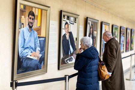 """Visitors examine Artist Betsy Ashton's exhibition, """"Portraits of Immigrants: Unknown Faces, Untold Stories"""" at Riverside Church in New York, U.S., March 10, 2019.  REUTERS/Demetrius Freeman"""