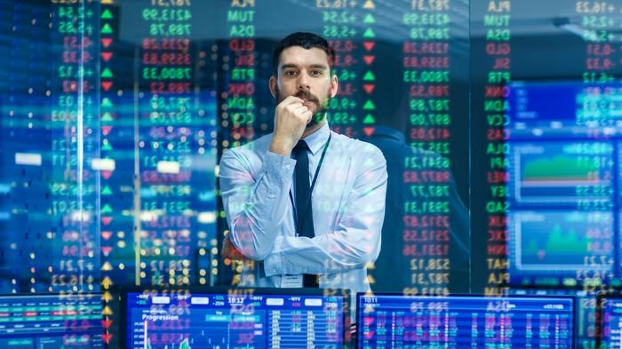 A man in a shirt and tie watches stock ticker numbers and graphs.