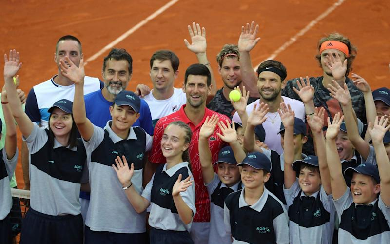 Novak Djokovic, in red, poses with other players and ballkids last month at the Adria Tour, where social distancing was ignored with predictable results   - Marko Djurica/Reuters
