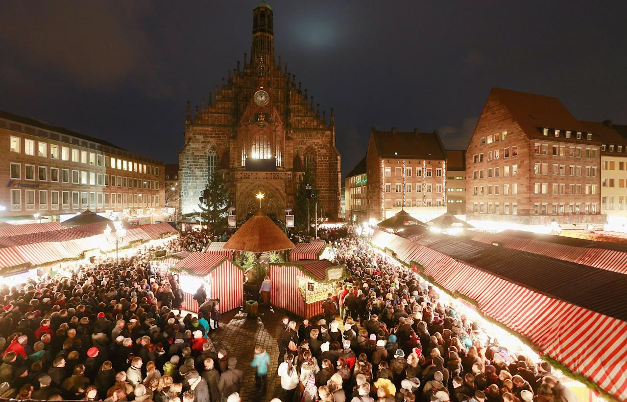 NUREMBERG, GERMANY - NOVEMBER 30:  Visitors attend the opening ceremony of the traditional Christmas market 'Nuernberger Christkindlesmarkt' on November 30, 2012 in Nuremberg, Germany. Originating in the 16th century the Nuremberg Christmas market is seen as one of the oldest of its kind in Germany.  (Photo by Johannes Simon/Getty Images)