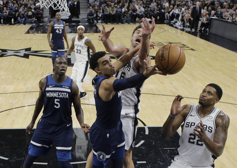 Minnesota Timberwolves guard Tyus Jones (1) tires to score past San Antonio Spurs center Pau Gasol (16) and forward Rudy Gay, right, during the first half of an NBA basketball game, Wednesday, Oct. 17, 2018, in San Antonio. (AP Photo/Eric Gay)