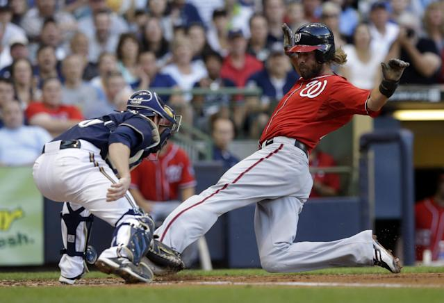 Washington Nationals' Jayson Werth slides safely past Milwaukee Brewers catcher Jonathan Lucroy during the second inning of a baseball game Saturday, Aug. 3, 2013, in Milwaukee. Werth scored from third on a sacrifice fly by Anthony Rendon. (AP Photo/Morry Gash)