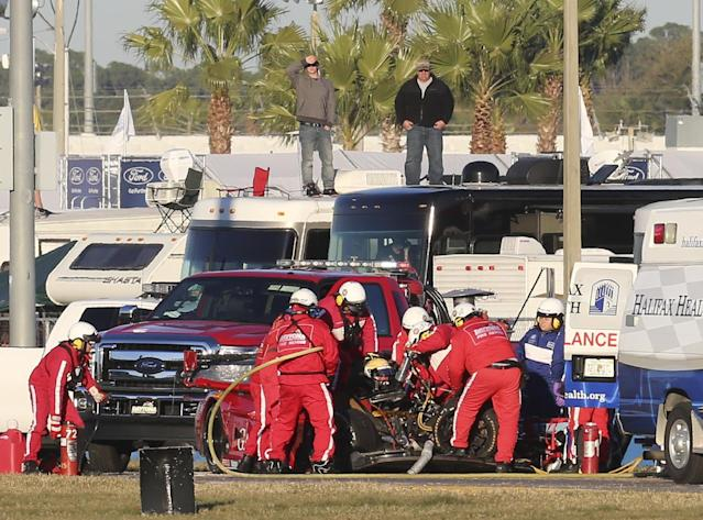 Rescue workers remove Memo Gidley, center, from his Corvette DP after he was involved in a crash during the IMSA Series Rolex 24 hour auto race at Daytona International Speedway in Daytona Beach, Fla., Saturday, Jan. 25, 2014. (AP Photo/David Graham)