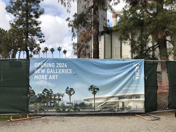 """A banner outside of the LACMA demolition zone shows a rendering for the new Peter Zumthor-designed building. It reads """"New Galleries, More Art."""" Demolition of the museum's Bing Theater began on April 6. <span class=""""copyright"""">(Carolina A. Miranda / Los Angeles Times)</span>"""