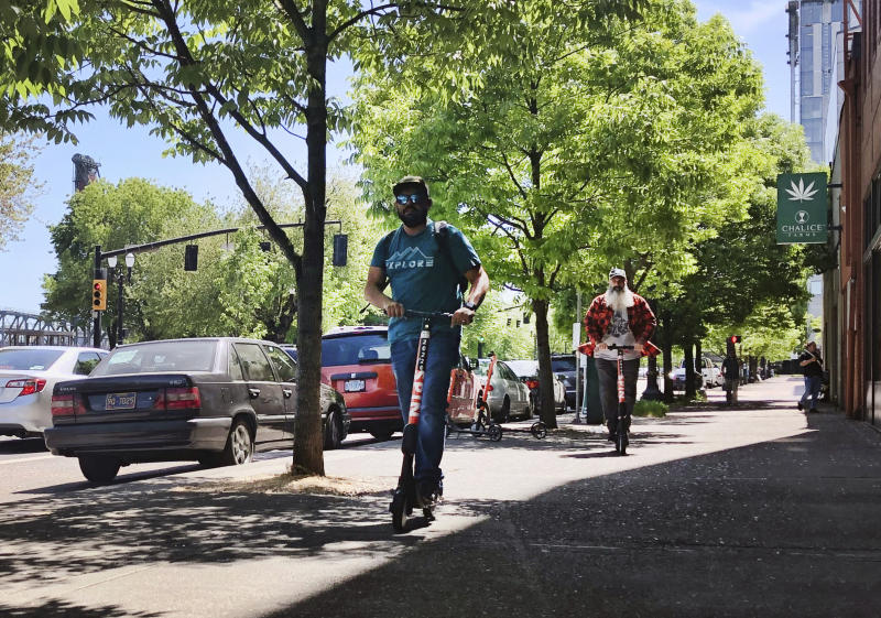 Motorists ride on electric scooters along a street in downtown Portland, Ore., Thursday, May 9, 2019. A disability rights nonprofit group in Oregon filed a letter of complaint Thursday with the city of Portland over new rules about an electric scooter pilot program. (AP Photo/Gillian Flaccus)