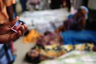 A Bangladeshi man holds his sister's portrait as he attempts to identify her among the bodies of those killed in the collapse of an eight-storey building in Savar, on the outskirts of Dhaka, on April 25, 2013