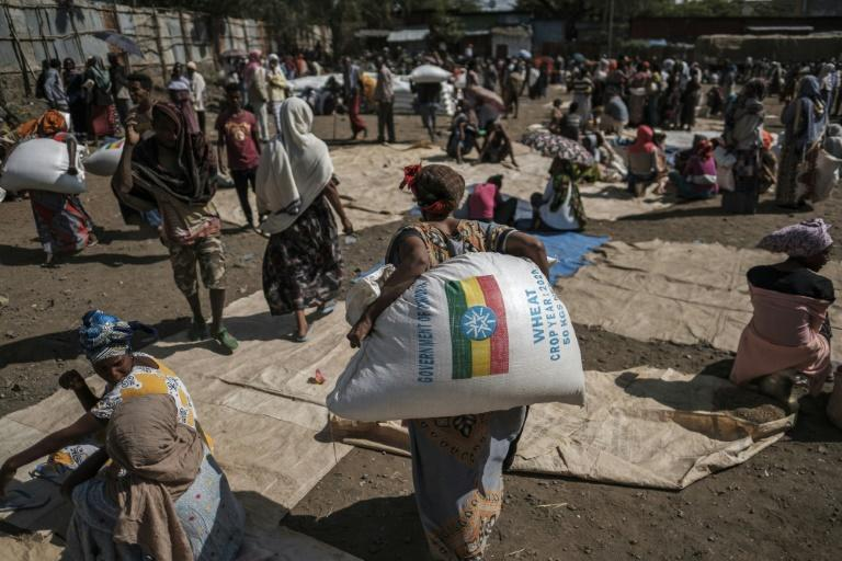 Residents in the Tigray town of Alamata collect sacks of wheat distributed by officials