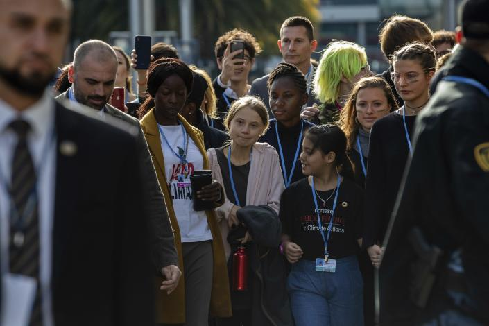 Climate activist Greta Thunberg, center and left, walks at the COP25 climate talks summit in Madrid, Friday Dec. 6, 2019. Thunberg arrived in Madrid Friday to join thousands of other young people in a march to demand world leaders take real action against climate change. (AP Photo/Bernat Armangue)