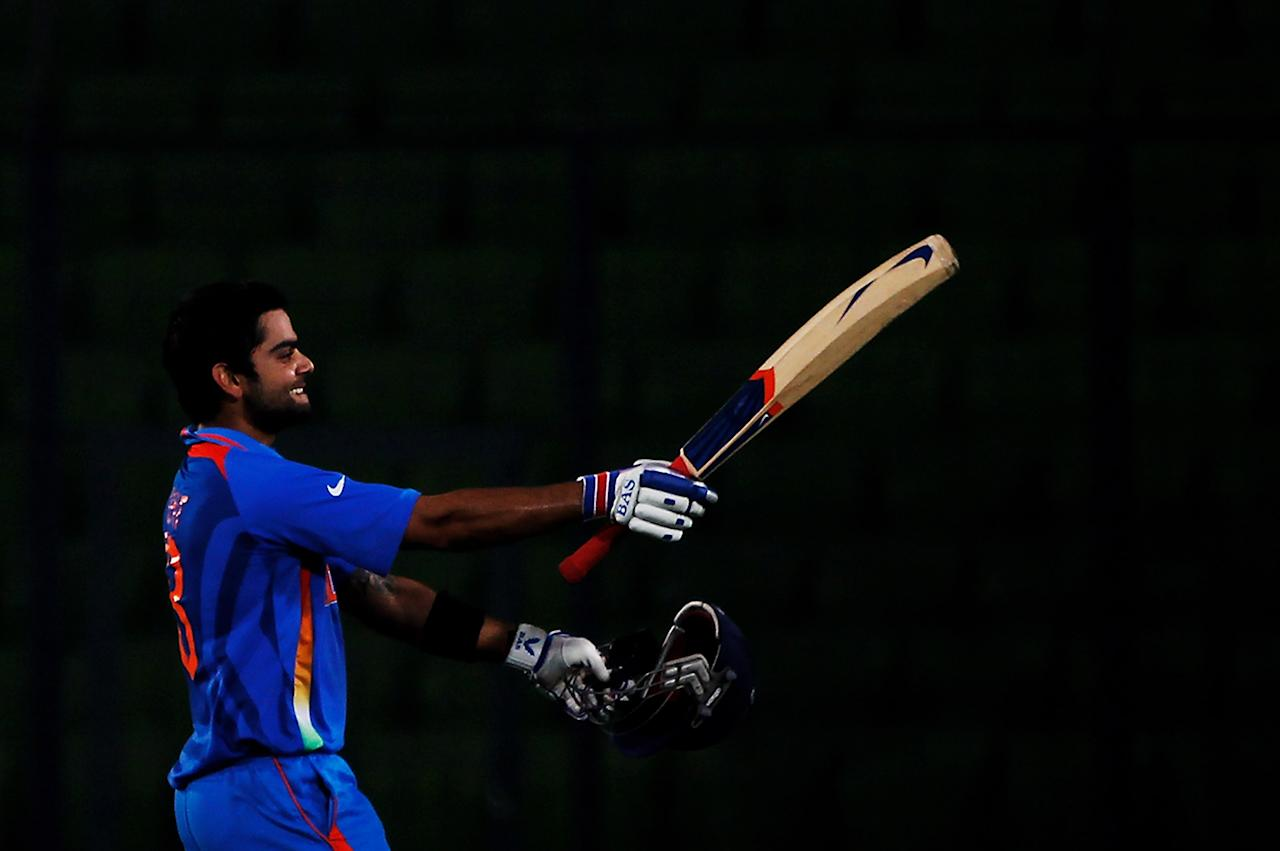 DHAKA, BANGLADESH - FEBRUARY 19:  Virat Kohli of India raises his bat on reaching his century during the opening game of the ICC Cricket World Cup between Bangladesh and India at the Shere-e-Bangla National Stadium on February 19, 2011 in Dhaka, Bangladesh.  (Photo by Daniel Berehulak/Getty Images)