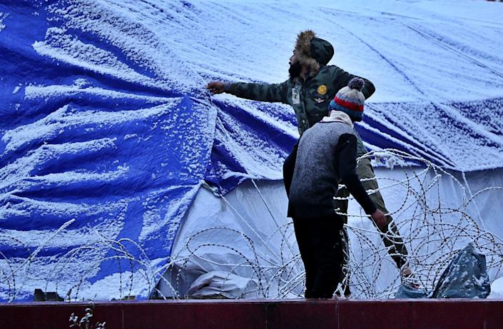 Protesters shake the snow off their tent in Tahrir Square in Baghdad, Iraq, Tuesday, Feb. 11, 2020: (AP Photo/Hadi Mizban)