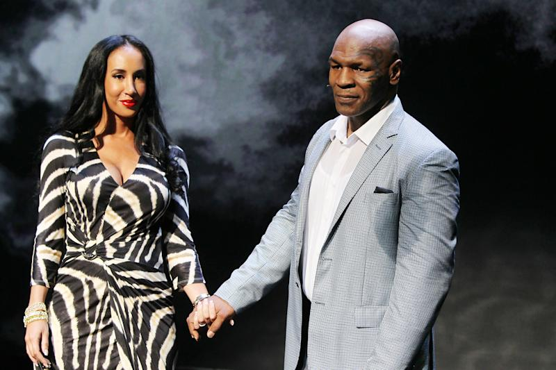 """This image released by Starpix shows, former boxer Mike Tyson, right, holds hands with his wife Kiki Tyson at the curtain call for the opening night of """"Mike Tyson: Undisputed Truth,"""" Thursday, Aug. 2, 2012 at the Longacre Theatre in New York. The one man show starring Tyson was directed by Spike Lee, and written by Kiki Tyson. (AP Photo/Starpix, Amanda Schwab)"""