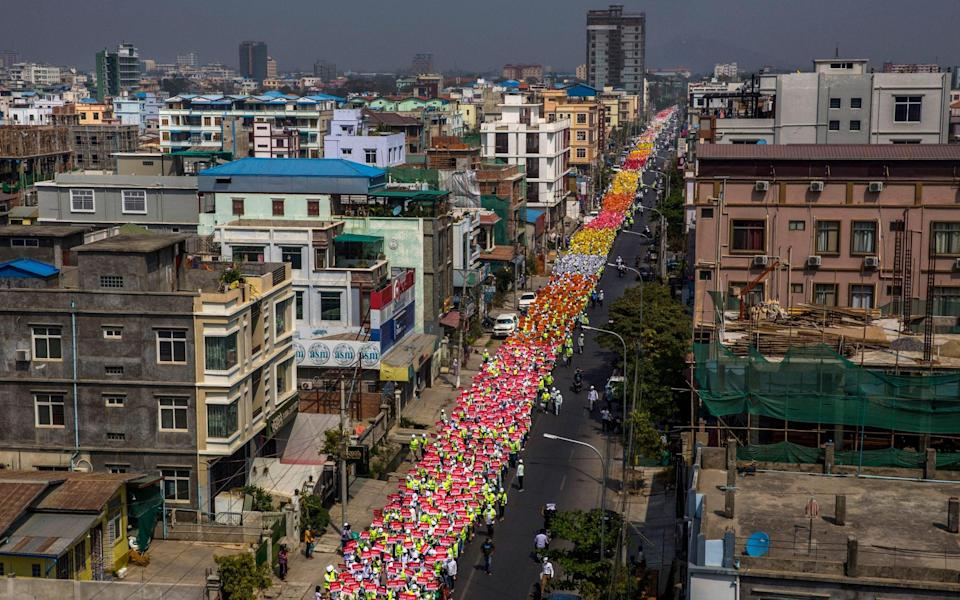 People march along a street in Mandalay, Myanmar - THE NEW YORK TIMES