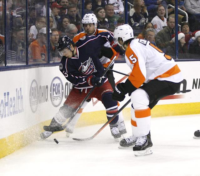 Columbus Blue Jackets' Cam Atkinson (13) is pressured by Philadelphia Flyers' Mark Streit (32) and Braydon Coburn (5) during the second period of an NHL hockey game on Saturday, Dec. 21, 2013, in Columbus, Ohio. (AP Photo/Mike Munden)