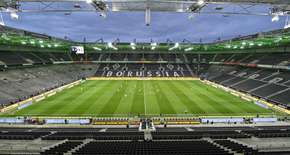 Players run for the ball in an empty stadium during the German Bundesliga soccer match between Borussia Moenchengladbach and 1.FC Cologne in Moenchengladbach, Germany, Wednesday, March 11, 2020. It is the first Bundesliga match played behind closed doors without spectators due to the coronavirus outbreak. For most people, the new coronavirus causes only mild or moderate symptoms, such as fever and cough. For some, especially older adults and people with existing health problems, it can cause more severe illness, including pneumonia. (AP Photo/Martin Meissner)