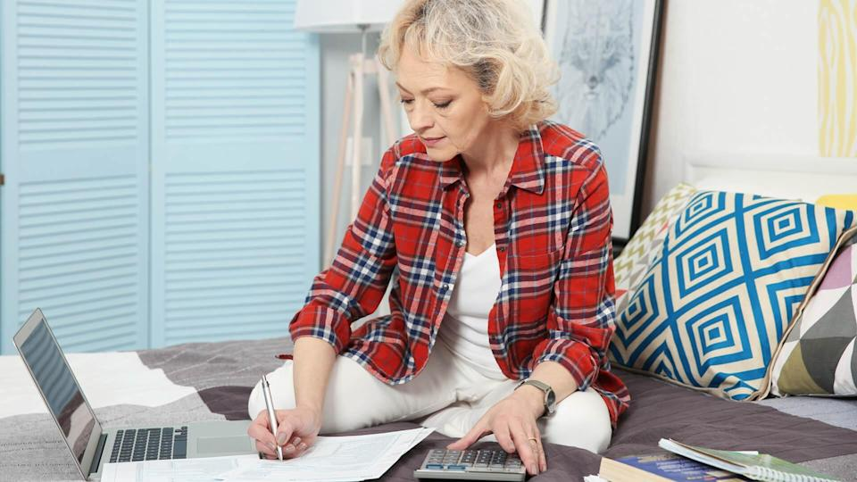 Mature woman on bed calculating bills