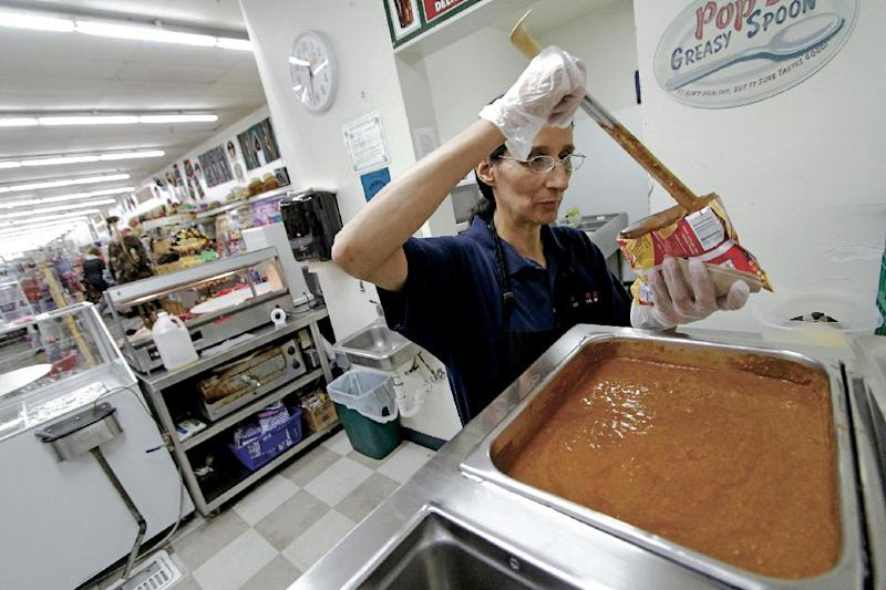 "In this Sept. 27, 2013 photo, Loraine Chavez, of Santa Fe, prepares a Frito Pie for a costumer at the Five & Dime in Santa Fe, N.M. The tourist attraction and a mainstay in the city's historic plaza was recently insulted by food critic Anthony Bourdain on an episode of CNN's ""Parts Unknown"". (AP Photo/The Santa Fe New Mexican, Luis Sanchez Saturno)"