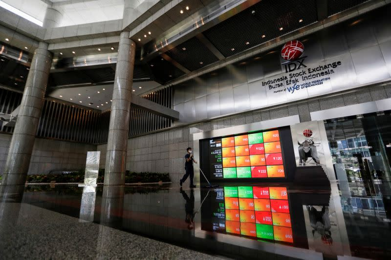 A worker wearing a protective mask cleans the floor near an electronic board displaying the stock market index at the Indonesia Stock Exchange (IDX), in Jakarta