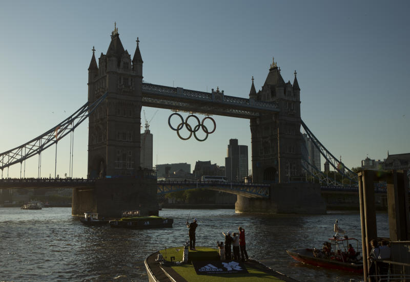 U.S. golfer Dustin Johnson, left, hits a shot as he and Spanish golfer Sergio Garcia, second left, take it in turns to hit golf balls at a floating golf hole on the River Thame as Olympic rings hang from Tower Bridge ahead of the 2012 Summer Olympics, Monday, July 23, 2012, in London. The two golfers took part in the stunt to promote a sportswear maker. Golf is set to be included as an Olympic sport in the next games in 2016. (AP Photo/Matt Dunham)