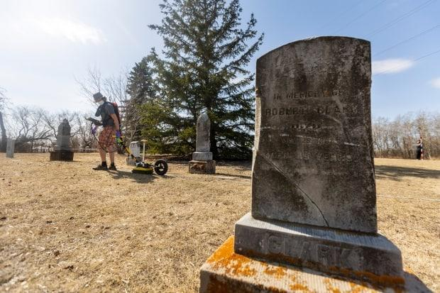 Spencer Lyons from the U of S uses a ground-penetrating radar to look for unmarked graves at Nutana Pioneer Cemetery. (Dave Stobbe - image credit)