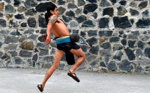 """A man plays a pre-Columbian ballgame called """"Ulama"""" -in Nahuatl indigenous language- which rule is to hit a """"Ulamaloni"""" (solid rubber ball) with the hip or shoulder, during a match at the FARO Poniente cultural center in Mexico City - Credit: AFP"""