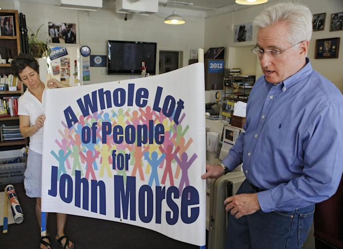 In this photo taken May 24, 2013, Democratic state Senate President John Morse, right, and Cristy Le Lait roll out a banner at the Democratic Party offices in Colorado Springs, Colo., that they plan to use to urge voters not to sign petitions for Morse's recall. Gun-rights activists with support of the National Rifle Association are seeking to ouster Morse for his support of new gun laws that restrict ammunition magazines and expand background checks to include private gun sales. (AP Photo/Ed Andrieski)