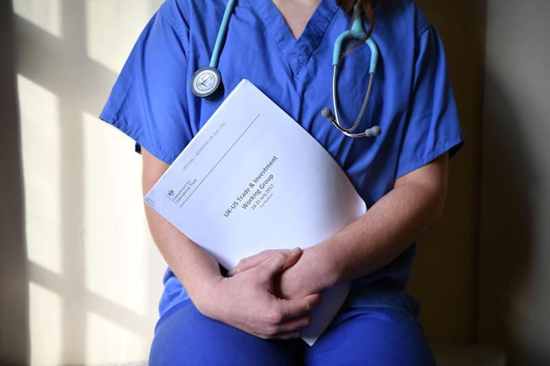 A member of NHS medical staff poses with unredacted documents related to post-Brexit UK-US Trade talks following a Labour election policy announcement on the NHS at church house n Westminster on November 27, 2019 in London, England. Photo: Leon Neal/Getty Images