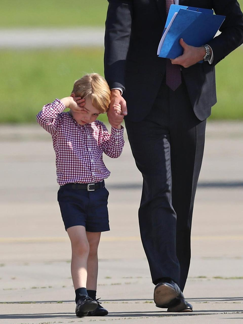 <p>George said goodbye to Germany in a checked shirt and navy tailored shorts. [Photo: PA] </p>